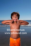 Portrait of a young hispanic boy on the beach making faces at the camera. Blue sky and ocean in the backghround,  Orange swim trunks.